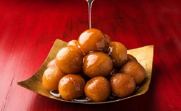 世界一甘いと言われているインドスイーツ「グラブジャムン」。お皿に盛られてシロップがかけられている様子。
