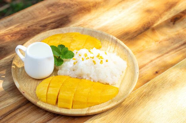 タイの定番スイーツ「 カオニャオ・マムアン」。お皿にもち米、マンゴー、コンデンスミルクが盛り付けられている。